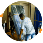 team of movers carefully moving a large item