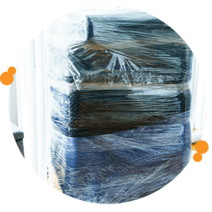 furniture wrapped in moving blankets and plastic wrap